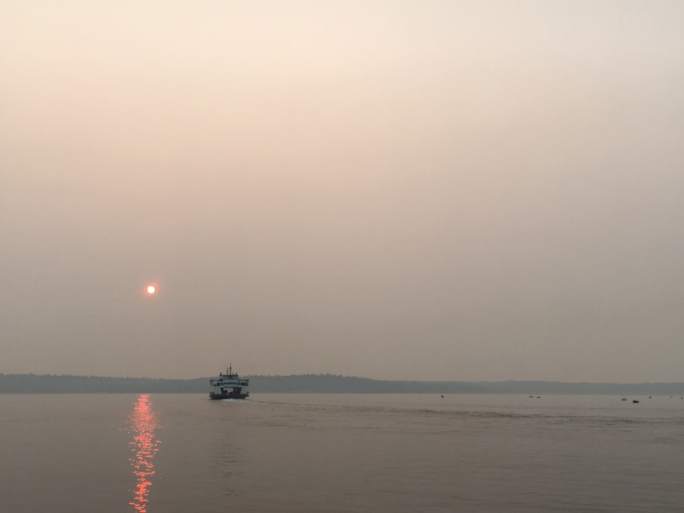 A ferry at sunset in the Puget Sound, the sky is very hazy because of smoke.