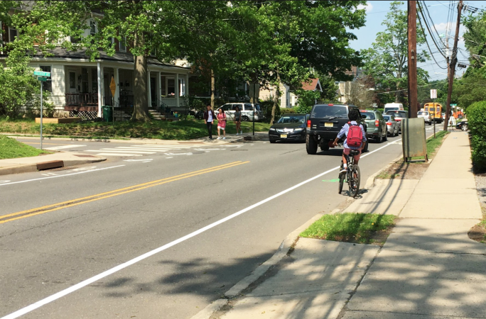 People walking down a sidewalk with a bike lane adjacent with a person riding a bike on a 2-lane street