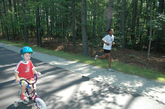 Photo of a child riding a bicycle and a runner both using a traditional greenway with a natural surface shoulder