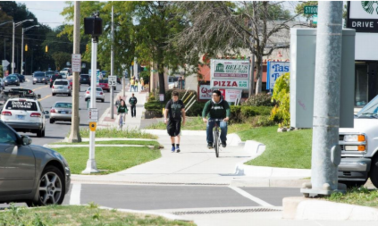 In the foreground one person walking and one person riding a bike on a multi-use sidepath with a turning vehicle at the upcoming intersection