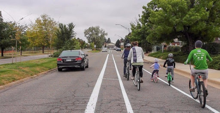 Photo of adults and children riding bicycles in a buffered bike lane on a street with a median
